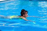 Middle-aged woman swims in the swimming pool