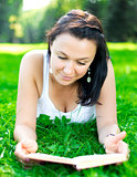Beautiful girl lying on a grass with book