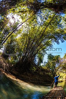 Man Steeting Bamboo Boat