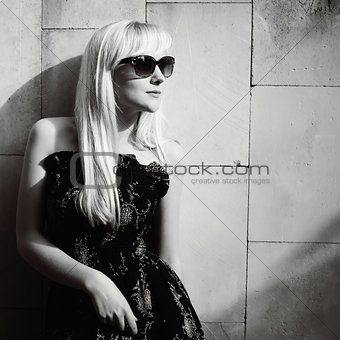 blond young woman posing against the white wall