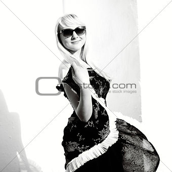 blond young woman posing by the white wall