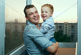Young father and son smiling on the balcony.