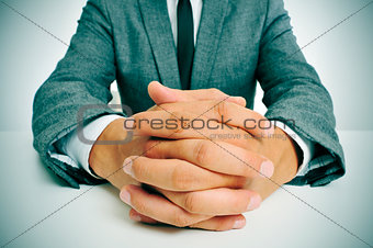 man in suit with clasped hands