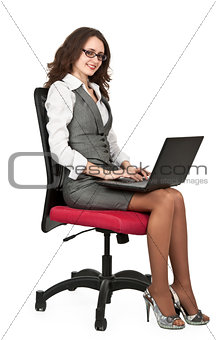 Business brunette girl on a chair with a laptop