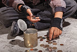 Beggar child counting coins sitting on damaged concrete floor
