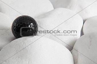 Black golf ball and white stones