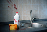 Bottle of dishwashing liquid with bloody fingerprints