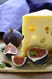 piece of cheese (Maasdam) with fresh figs on a wooden board