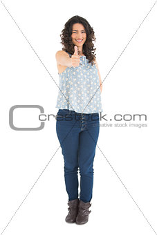 Smiling attractive brunette posing thumbs up