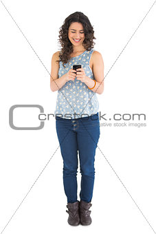 Smiling attractive brunette texting