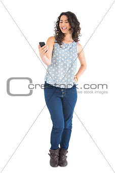 Cheerful attractive brunette looking at her smartphone