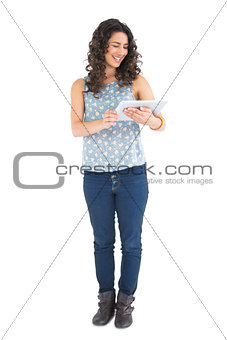 Smiling attractive brunette using her tablet