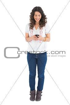 Attractive casual brunette sending text message