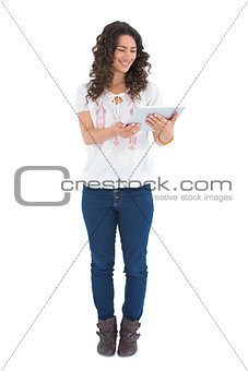 Attractive casual brunette using her tablet pc