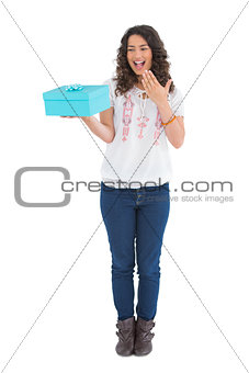 Surprised casual brunette holding a present