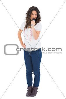 Cheerful pretty brunette singing with her microphone