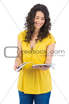 Smiling curly haired brunette reading magazine