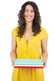 Cheerful curly haired brunette holding notebooks