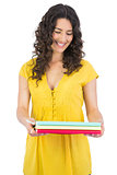 Happy curly haired brunette holding notebooks