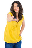 Cheerful curly haired pretty woman holding remote