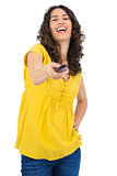 Cheerful curly haired pretty woman changing channel with remote