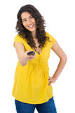 Smiling curly haired pretty woman changing channel with remote