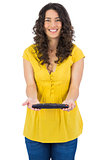 Cheerful casual young woman holding remote