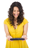 Happy casual young woman holding remote