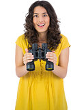 Smiling casual young woman holding binoculars