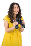 Serious casual young woman holding binoculars