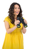 Cheerful casual young woman holding binoculars