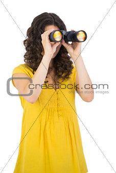 Casual young woman using binoculars