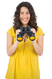 Cheerful casual young woman using binoculars