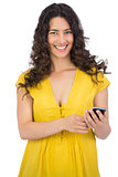 Smiling casual young woman sending text message