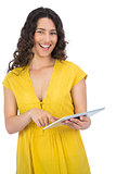 Smiling casual young woman scrolling on her tablet computer