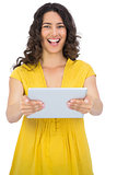 Happy casual young woman holding her tablet computer