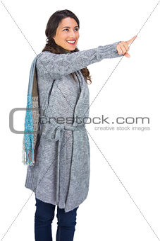 Smiling brunette wearing winter clothes pointing out