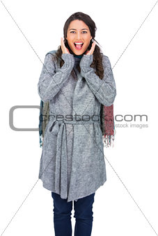 Surprised brunette wearing winter clothes posing