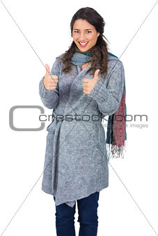 Cheerful pretty brunette wearing winter clothes posing thumb up