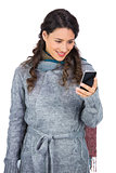 Pretty brunette wearing winter clothes holding her smartphone