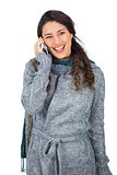 Smiling pretty brunette wearing winter clothes on the phone