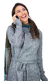 Smiling pretty brunette wearing winter clothes having phone call