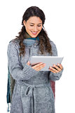 Smiling pretty brunette wearing winter clothes holding her tablet