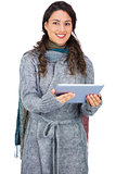 Cheerful pretty brunette wearing winter clothes holding her tablet