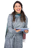 Happy pretty brunette wearing winter clothes holding her tablet