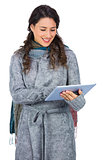 Relaxed brunette wearing winter clothes holding her tablet