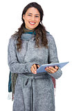 Smiling model wearing winter clothes holding her tablet