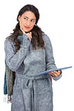 Pensive model wearing winter clothes holding her tablet