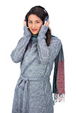 Beautiful model wearing winter clothes listening to music