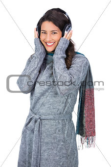 Smiling beautiful model wearing winter clothes listening to music
